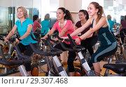 Купить «Females cycling in sport club», фото № 29307468, снято 9 декабря 2018 г. (c) Яков Филимонов / Фотобанк Лори