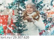 Купить «Adult woman is choosing decorative Christmas tree in the market», фото № 29307620, снято 21 декабря 2017 г. (c) Яков Филимонов / Фотобанк Лори