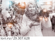 Купить «Adult woman is choosing Christmas wreath for house in the market», фото № 29307628, снято 21 декабря 2017 г. (c) Яков Филимонов / Фотобанк Лори