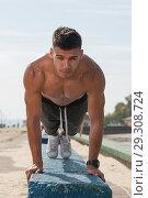 Купить «Portrait of young strong man training core muscles», фото № 29308724, снято 9 сентября 2018 г. (c) Pavel Biryukov / Фотобанк Лори