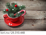 Купить «Christmas decorations in red cup on wooden background», фото № 29310448, снято 26 октября 2018 г. (c) Майя Крученкова / Фотобанк Лори