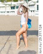 Купить «Young female in swimsuit with hat and bag walking at beach», фото № 29311124, снято 10 июля 2018 г. (c) Яков Филимонов / Фотобанк Лори