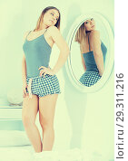 Купить «Young female in pygama, using mirror in bedroom», фото № 29311216, снято 5 марта 2018 г. (c) Яков Филимонов / Фотобанк Лори