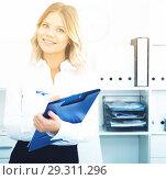 Купить «Well-wishing girl with folder of documents is standing in well-lit office», фото № 29311296, снято 17 октября 2017 г. (c) Яков Филимонов / Фотобанк Лори