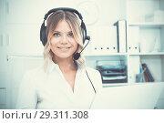 Купить «Young call center employee in headphones is sitting near laptop in the office», фото № 29311308, снято 17 октября 2017 г. (c) Яков Филимонов / Фотобанк Лори