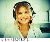 Купить «Young call center employee in headphones is sitting near laptop in the office», фото № 29311312, снято 17 октября 2017 г. (c) Яков Филимонов / Фотобанк Лори