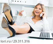 Купить «Laid-back girl in corporate-type clothes puts her feet on table and speaks by phone in office», фото № 29311316, снято 17 октября 2017 г. (c) Яков Филимонов / Фотобанк Лори