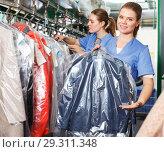 Купить «Worker of laundry demonstrating clean garment», фото № 29311348, снято 9 мая 2018 г. (c) Яков Филимонов / Фотобанк Лори