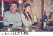 Купить «Young emotional couple quarreled in restaurant sitting at served», фото № 29311488, снято 18 декабря 2017 г. (c) Яков Филимонов / Фотобанк Лори