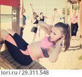 Купить «Focusing woman doing workout on beach in sunny morning», фото № 29311548, снято 14 июня 2017 г. (c) Яков Филимонов / Фотобанк Лори