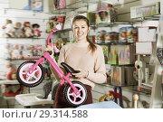 Купить «Young woman holding balance bicycle in the shop of goods for chi», фото № 29314588, снято 19 декабря 2017 г. (c) Яков Филимонов / Фотобанк Лори