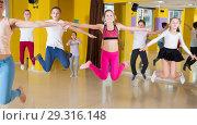 Купить «Children with teacher jumping in dance hall», фото № 29316148, снято 3 марта 2018 г. (c) Яков Филимонов / Фотобанк Лори