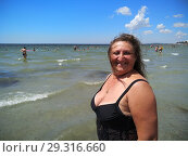 Portrait of a middle-aged woman in a black bathing suit against the sea. Стоковое фото, фотограф Дмитрий Морозов / Фотобанк Лори