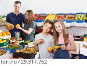 Купить «Preteen boy and girl holding fresh fruits, parents on background», фото № 29317752, снято 23 июня 2018 г. (c) Яков Филимонов / Фотобанк Лори