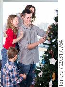 Купить «Smiling family members preparing for Christmas», фото № 29317764, снято 23 января 2019 г. (c) Яков Филимонов / Фотобанк Лори