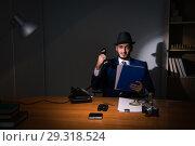 Купить «Detective sitting in dark room in vintage concept», фото № 29318524, снято 13 июля 2017 г. (c) Elnur / Фотобанк Лори