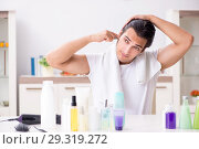 Купить «Young handsome man in the bathroom in hygiene concept», фото № 29319272, снято 19 июля 2018 г. (c) Elnur / Фотобанк Лори