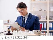 Купить «Young lawyer playing chess to train his court strategy and tacti», фото № 29320344, снято 31 июля 2018 г. (c) Elnur / Фотобанк Лори