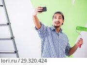 Купить «Young painter doing renovation at home», фото № 29320424, снято 2 мая 2018 г. (c) Elnur / Фотобанк Лори
