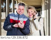 Купить «middle-aged husband and wife go nearby with each other and speak by mobile phone», фото № 29336872, снято 20 августа 2019 г. (c) Яков Филимонов / Фотобанк Лори