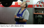 Купить «Confident male car mechanic in workshop writing job sheet for repairs of vehicle», видеоролик № 29364416, снято 27 сентября 2018 г. (c) Яков Филимонов / Фотобанк Лори