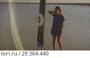 Купить «Slim sexy girl enjoying sunset, stands near a wooden salt pillar of a salt lake», видеоролик № 29364440, снято 28 октября 2018 г. (c) Ирина Мойсеева / Фотобанк Лори