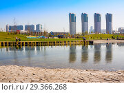 "Купить «New city landscape park ""Khodynskoe field"" with pond and modern skyscrapers, Moscow, Russia. It opened in september of 2018. Total area of park is about 25 hectares», фото № 29366268, снято 18 октября 2018 г. (c) Papoyan Irina / Фотобанк Лори"
