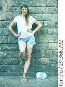 Купить «Young woman standing near old stone wall», фото № 29366792, снято 15 августа 2017 г. (c) Яков Филимонов / Фотобанк Лори