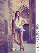 Купить «Young woman standing near old stone wall», фото № 29366800, снято 15 августа 2017 г. (c) Яков Филимонов / Фотобанк Лори