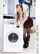 Купить «Woman consulted on phone about buying of washer», фото № 29366916, снято 12 декабря 2017 г. (c) Яков Филимонов / Фотобанк Лори
