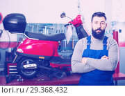 Купить «friendly man worker displaying his workplace in motorcycle workshop», фото № 29368432, снято 16 декабря 2018 г. (c) Яков Филимонов / Фотобанк Лори