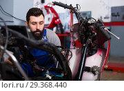 Купить «Worker repairing motorbike», фото № 29368440, снято 11 декабря 2018 г. (c) Яков Филимонов / Фотобанк Лори