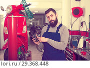 Купить «Beardy guy is calculating sum for repairing motorcycle», фото № 29368448, снято 16 декабря 2018 г. (c) Яков Филимонов / Фотобанк Лори