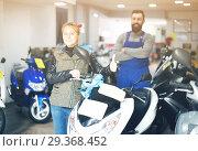 Купить «Worker with woman customer in motorcycle workplace», фото № 29368452, снято 12 декабря 2018 г. (c) Яков Филимонов / Фотобанк Лори