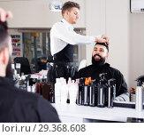 Купить «smiling male stylist creating haircut for man client at hairdressing salon», фото № 29368608, снято 27 января 2017 г. (c) Яков Филимонов / Фотобанк Лори