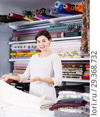 Купить «Seller showing white fabric», фото № 29368732, снято 4 января 2017 г. (c) Яков Филимонов / Фотобанк Лори