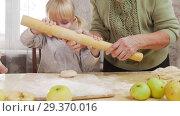 Купить «Family making little pies. A little girl bites a raw dough and rolls out the dough», видеоролик № 29370016, снято 6 июля 2020 г. (c) Константин Шишкин / Фотобанк Лори