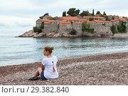 Купить «European woman sitting on the luxury beach against Sveti Stefan hotel and resort. Adriatic sea, Montenegro. Europa», фото № 29382840, снято 3 июня 2016 г. (c) Кекяляйнен Андрей / Фотобанк Лори
