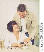 Купить «Son telling brunette mother how to use phone», фото № 29383332, снято 9 декабря 2019 г. (c) Яков Филимонов / Фотобанк Лори
