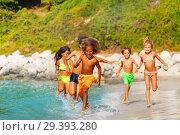 Купить «Boy running along sandy beach with his friends», фото № 29393280, снято 22 июля 2018 г. (c) Сергей Новиков / Фотобанк Лори