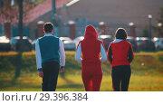 Купить «People in sport costumes walking in park. Back angle», видеоролик № 29396384, снято 23 июля 2019 г. (c) Константин Шишкин / Фотобанк Лори