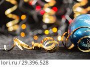 Купить «Party Background with Christmas toy, lights and serpentine», фото № 29396528, снято 17 декабря 2018 г. (c) Владимир Пойлов / Фотобанк Лори