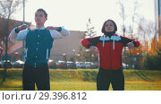 Купить «Two young woman and a man in sport costumes warming up», видеоролик № 29396812, снято 23 июля 2019 г. (c) Константин Шишкин / Фотобанк Лори