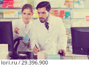 Купить «Two pharmacists are attentively stocktaking medicines with computer and note on paper», фото № 29396900, снято 28 февраля 2018 г. (c) Яков Филимонов / Фотобанк Лори