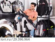 Купить «Young man is choosing new jacket for motorbike», фото № 29396964, снято 1 сентября 2017 г. (c) Яков Филимонов / Фотобанк Лори