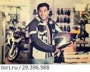 Купить «Man in moto equipment store», фото № 29396988, снято 1 сентября 2017 г. (c) Яков Филимонов / Фотобанк Лори
