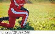 Купить «People in sport costumes doing leg lunges in park», видеоролик № 29397248, снято 23 июля 2019 г. (c) Константин Шишкин / Фотобанк Лори