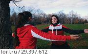Купить «Two young woman in sport costumes doing exercises in park», видеоролик № 29397612, снято 23 июля 2019 г. (c) Константин Шишкин / Фотобанк Лори