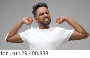 Купить «indian man stretching over grey background», видеоролик № 29400888, снято 1 ноября 2018 г. (c) Syda Productions / Фотобанк Лори
