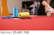 Купить «Young woman at sewing factory cutting the cloth. Sewing thread in focus. Static shot», видеоролик № 29401100, снято 10 декабря 2018 г. (c) Константин Шишкин / Фотобанк Лори